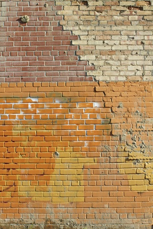 worn structure: Old exterior brick wall, multicolored with cracks and repairs revealing evidence of the buildings past. Vertical, copy space.