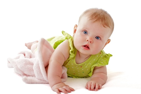 Bright blue eyed 6 month old baby girl in lime green dress on her tummy with a soft blanket. Horizontal, isolated on white background, copy space. photo