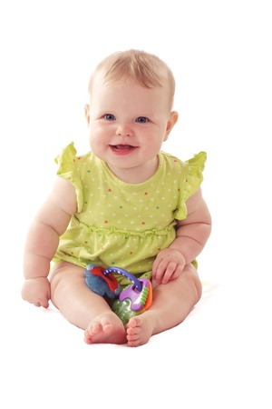 Laughing 6 month old baby girl with big blue eyes and ruffled dress sits with a rattle. Pastels, isolated on white background, vertical, copy space. photo