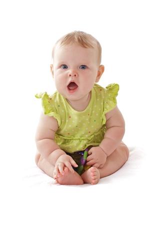 Pretty 6 měsíců starou holčičku s velkýma modrýma očima a volánky šaty sedí a vocalizes. Ona má chrastítko. Pastely, izolovaných na bílém pozadí, vertikální, copy space. Reklamní fotografie