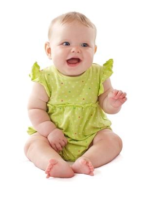 Rire fille bébé de 6 mois en position assise et en agitant son bras. Pastels, isolé sur fond blanc, vertical, copie, espace,. Banque d'images