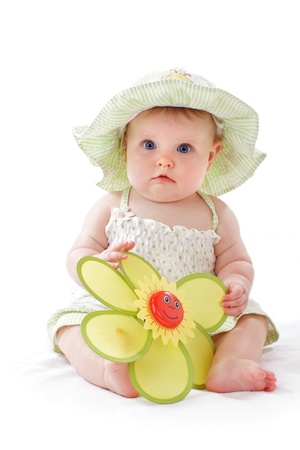 Happy beautiful 6 month old baby girl in green seersucker sun hat and sun dress sits and plays with a big yellow toy daisy. Pastels, isolated on white background, vertical, copy space. photo