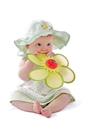 Happy beautiful 6 month old baby girl in green seersucker sun hat and sun dress sits and plays with a big yellow toy daisy. Pastels, isolated on white background, vertical, copy space. Banco de Imagens