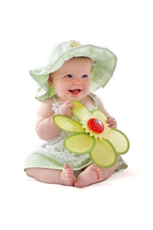 Šťastná krásná 6 měsíců starou holčičku v zelené Seersucker pokrývku a slunce šaty sedí a hraje si s velkým žlutým hračky daisy. Pastely, izolovaných na bílém pozadí, vertikální, copy space.