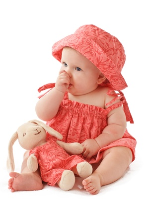 Sleepy 6 month old baby girl sits sucking her thumb and holds a stuffed toy bunny rabbit. Babys strawberry pink floral hat and sun dress match the toy. Vertical, copy space, isolated on white.