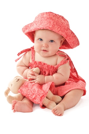 Smiling 6 month old baby girl sits holding a stuffed toy bunny rabbit. Babys strawberry pink floral hat and sun dress match the toy. Vertical, copy space, isolated on white. photo