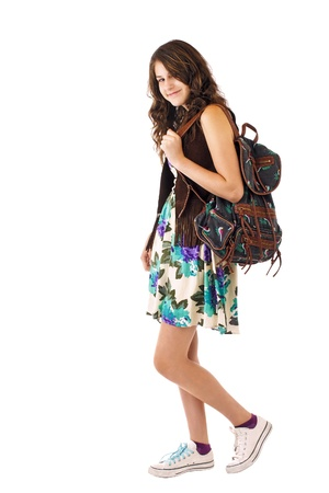 bookbag: Pretty smiling teenage girl in flowered dress and fringed vest carries a backpack. Vertical, isolated on white, copy space.