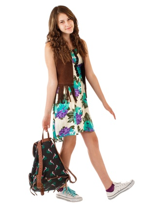 Pretty smiling teenage girl in flowered dress and fringed vest carries a backpack. Vertical, isolated on white, copy space.