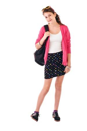 falda corta: Muy sonriente niña adolescente en la parte trasera de moda ropa para la escuela lleva una mochila al hombro. Suéter de color rosa, gafas de sol en la parte superior de la cabeza, falda negro corto. Vertical aislado, en blanco, copia espacio. Foto de archivo