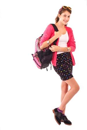 detras de: Muy sonriente niña adolescente en la parte trasera de moda ropa para la escuela lleva una mochila al hombro. Suéter de color rosa, gafas de sol en la parte superior de la cabeza, falda negro corto. Vertical aislado, en blanco, copia espacio. Foto de archivo