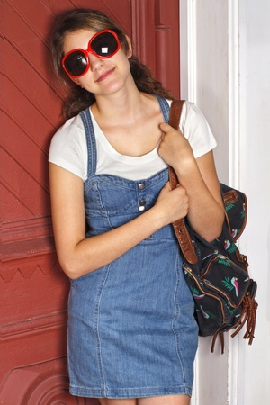 Pretty smiling teenage girl in sunglasses and fashionable back to school denim dress. She carries a backpack and leans against old red door. Vertical, copy space. Stock Photo