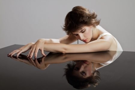 Beautiful glamorous young dark haired woman rests bare arms on reflective surface