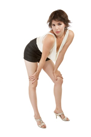 knees bent: Glamorous sexy dark-haired woman in her early 20s stands in flirtatious bent forward pose with hands on knees Stock Photo