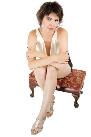 early 20s: Glamorous sexy morena mujer, de 20 a�os, sentado sobre taburete tapizado bajo con los brazos y los tobillos cruzados Foto de archivo