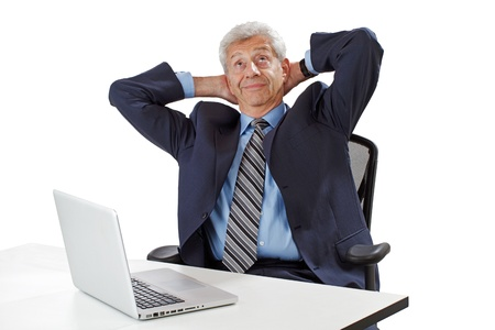 Smiling senior business man leans back from desk with arms clasped behind head photo