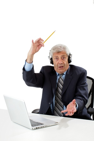 imagining: Senior business man sitting at desk wears headphones, waves pencil, full of ideas. Isolated on white, vertical, copy space.