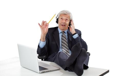 S úsměvem senior business člověk relaxuje s nohama nahoře na stole, nosí sluchátka, vlny tužku, si myslí, že z nápadů. Izolovaných na bílém, horizontální, copy space. Reklamní fotografie