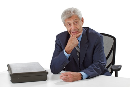 Senior business man in dark suit with closed briefcase sits at desk. He leans forward attentively, hand on chin. Horizontal, isolated on white, copy space. photo