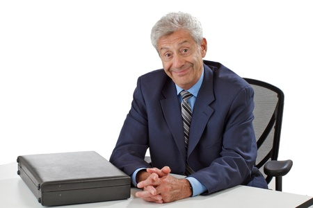 Cheerful senior business man in dark suit with closed briefcase leans forward, hands folded on desk. Horizontal, isolated on white, copy space. photo