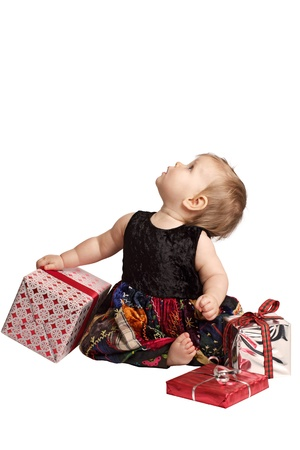 velvet dress: Curious baby in velvet embroidered patchwork dress sits with festive holiday gifts, tilts head back and looks up. Vertical, isolatedcut out on white background, copy space.