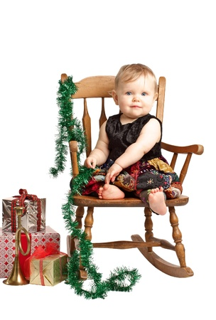 velvet dress: Pretty smiling baby in velvet embroidered patchwork dress sits in rocking chair with festive holiday gifts and garland