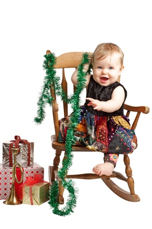 Cute laughing baby in velvet embroidered patchwork dress sits in rocking chair with festive holiday gifts and garland. Vertical, isolatedcut out on white background, copy space. photo