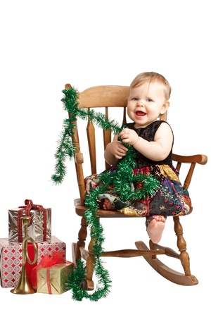 sits on a chair: Cute laughing baby in velvet embroidered patchwork dress sits in rocking chair with festive holiday gifts and garland. Vertical, isolatedcut out on white background, copy space.