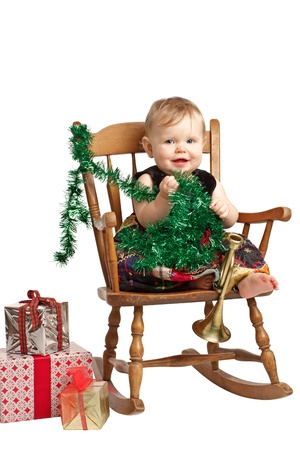 velvet dress: Cute laughing baby in velvet embroidered patchwork dress sits in rocking chair with festive holiday gifts and garland. Vertical, isolatedcut out on white background, copy space.