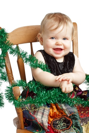 velvet dress: Cute laughing baby in velvet embroidered patchwork dress sits in rocking chair with festive garland. Vertical, isolatedcut out on white background, copy space.