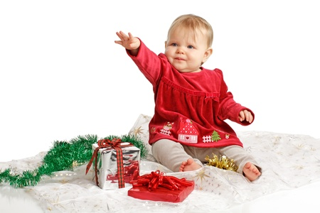 velvet dress: Smiling baby girl in red velvet dress and gray stretch pants raises one arm in a reaching gesture. She sits near wrapped holiday gifts and green garland. Isolatedcut out, white background, horizontal, copy space.