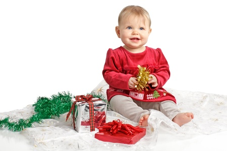 velvet dress: Smiling baby girl in red velvet dress and gray stretch pants holds shiny gold bow. She sits near wrapped holiday gifts and green garland. Isolatedcut out, white background, horizontal, copy space.