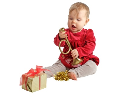 velvet dress: Sweet baby girl in red velvet dress and gray stretch pants inspects toy brass horn with curiosity. Wrapped holiday gift and gold bow nearby. Isolatedcut out, white background, horizontal, copy space. Stock Photo
