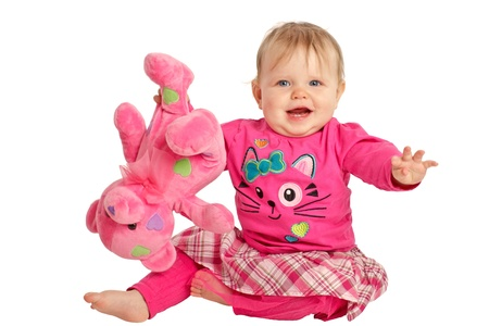 Happy active baby girl waves and holds pink teddy bear upside down. She wears pink shirt and tights with plaid skirt. Horizontal, isolatedcut out, white background, copy space. photo