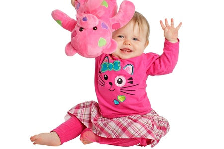 Happy active baby girl waves and holds pink teddy bear up high. She wears pink shirt and tights with plaid skirt. Horizontal, isolatedcut out, white background, copy space. photo
