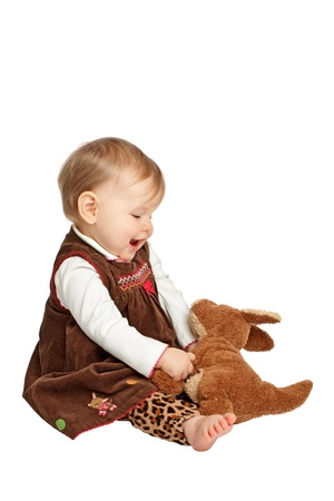 velvet dress: Delighted smiling baby girl sits sideways holding stuffed toy kangaroo. She has blue eyes, wispy hair, bare feet, and wears a brown velvet embroidered jumper with leopard print pants. Isolatedcut out on white background, vertical, copy space,