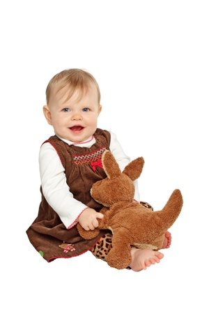 velvet dress: Smiling baby girl sits and plays with brown stuffed toy kangaroo. She has blue eyes, wispy blond hair, bare feet, and a brown velvet embroidered dress with leopard print pants. Isolatedcut out on white background, vertical, copy space. Stock Photo