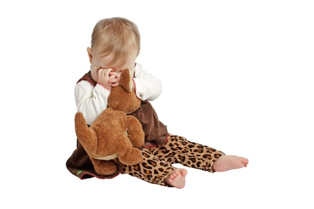 Sweet baby girl sits and plays peek-a-boo with brown stuffed toy kangaroo. She has wispy blond hair, bare feet, and a brown velvet embroidered dress with leopard print pants. Isolated/cut out on white background, vertical, copy space. photo