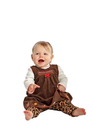 velvet dress: Laughing baby girl sits up. She has blue eyes, wispy hair, bare feet, and wears a brown velvet embroidered jumper with leopard print pants. Isolatedcut out on white background, vertical, copy space.