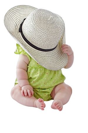 Happy 6 month old baby girl in green sun dress plays peekaboo with big straw hat