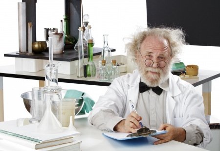 Eccentric senior scientist in lab holds pen and clipboard. High key, white background, horizontal, copy space.