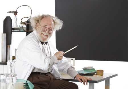 Cheerful eccentric senior scientist in his lab points to blackboard and explains his ideas. High key, horizontal, copy space. Stock Photo