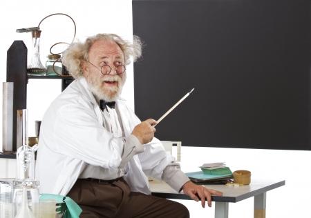 estereotipo: Alegre excéntrico científico de alto nivel en su laboratorio apunta a la pizarra y explica sus ideas. Alto clave, el espacio horizontal, copia. Foto de archivo
