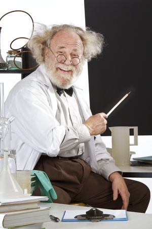 Cheerful eccentric senior scientist in his lab points to blackboard and explains his ideas  High key, vertical, copy space  Stock Photo
