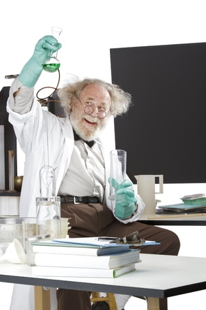 Cheerful mad senior scientist in lab measures green liquid in beaker  Frizzy grey hair, round glasses, lab coat, geek trousers, aqua rubber gloves, blank blackboard, vertical, high key, copy space  Stock Photo - 16963046