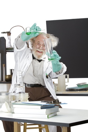 instructing: Cheerful mad senior scientist in lab measures green liquid in beaker  Frizzy grey hair, round glasses, lab coat, geek trousers, aqua rubber gloves, blank blackboard, vertical, high key, copy space