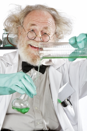 instructing: Cheerful mad senior scientist in lab measures green liquid in beaker  Closeup, frizzy grey hair, round glasses, lab coat, aqua rubber gloves, vertical, high key  Stock Photo