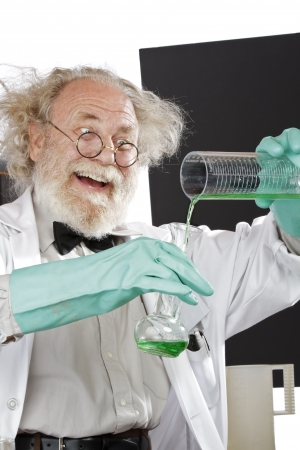 Cheerful mad senior scientist in lab measures green liquid in beaker  Frizzy grey hair, round glasses, lab coat, aqua rubber gloves, blank blackboard, vertical, high key, copy space  Stock Photo - 16963079