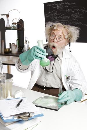 Divit šílený vedoucí vědecký pracovník v laboratoři reaguje na napěnění zelenou kapalinu přetékání kádinka kudrnaté šedé vlasy, kulaté brýle, plášť, aqua gumové rukavice, prázdné tabule, vertikální, high key, copy space