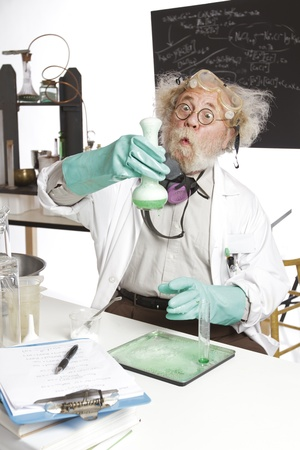 Amazed mad senior scientist in lab reacts to foaming green liquid overflowing beaker  Frizzy grey hair, round glasses, lab coat, aqua rubber gloves, blank blackboard, vertical, high key, copy space  photo