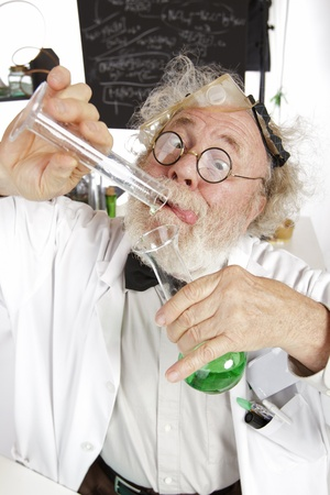 Mad senior scientist in lab concentrates on pouring green liquid into beaker  Frizzy grey hair, round glasses, lab coat, blackboard, vertical, high key, copy space  Stock Photo - 16963055